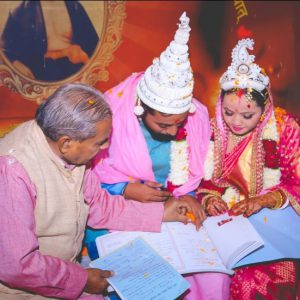 A newly married couple signing the marriage register, India, 2018